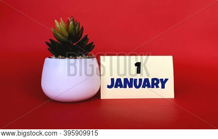 January 1 On A Yellow Sticker.next To It Is A Pot With A Flower On A Red Background .beginning Of Ye