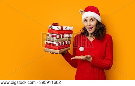 Beautiful Young Girl In Santa Claus Hat Holds Gifts On Bright Orange Background. New Year And Christ