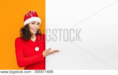 Young Girl In Santa Claus Hat On Bright Color Background Make Gesture Hand. New Year And Christmas C