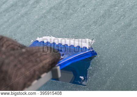 A Blue Plastic Scraper Hold By A Hand In Black Glove At A Windshield