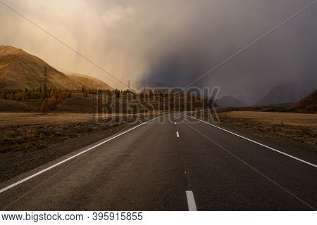 Amazing Autumn Landscape With An Asphalt Road Through The Steppe, Mountains Covered With A Golden Fo