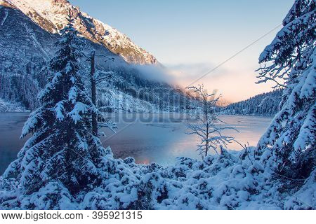 Winter Sunrise Over Scenic Frozen Lake In Mountains. Winter Mountains. Scenic Winter Landscape. Snow