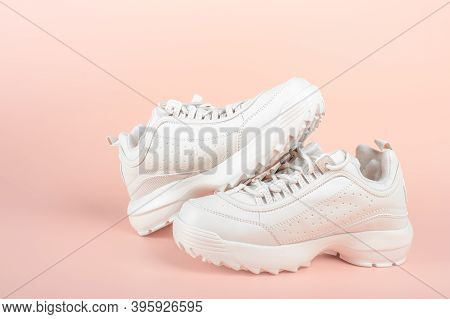 White Sneakers On Light Pink Background. Womens Shoes. Stylish White Sneakers. Pair Of Trendy Sneake