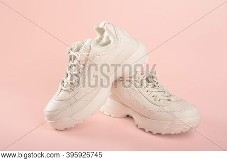 White Sneakers On Light Pink Background. Pair Of Trendy Women's Sneakers On Pastel Background. Sport