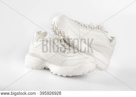 White Sneakers On White Background. Pair Of Trendy Women's Sneakers On White. Sports Shoes For Cold