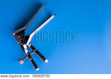Gynecological Speculum On A Light Blue Background. Copy Space Gynecological Examination Tool.