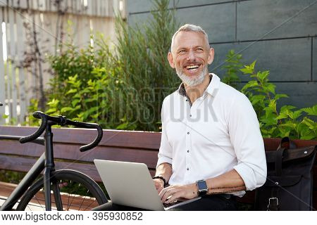 Happy Guy. Successful Modern Middle Aged Businessman In Stylish Suit Smiling Aside While Working On