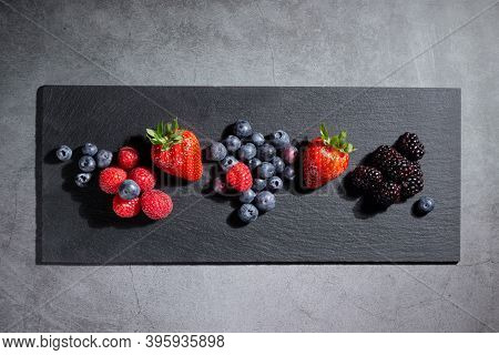 Assorted Berries On Slate Plate On Dark Background Top View.