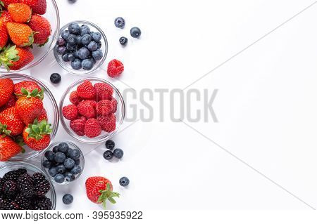 Berries In Glass Bowls  On White Background With Copy Space . Top View.