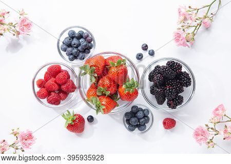 Berries In Glass Bowls And Roses On White Background. Top View.