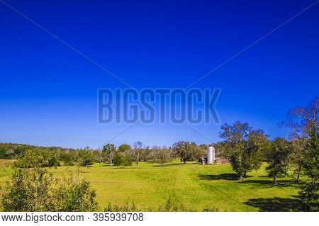 Beautiful Farm Land With Trees And Blue Skys Distant View