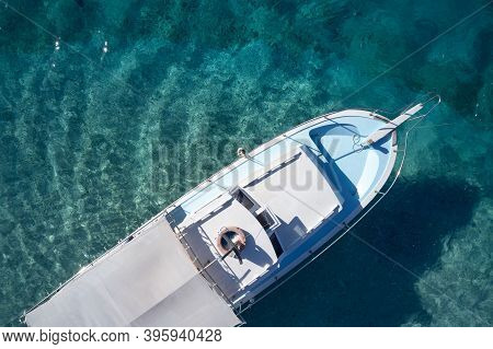 Top View Of Boat On Clear Turquoise Water. Empty Boat Floating On Crystal Ocean Water. View From Abo
