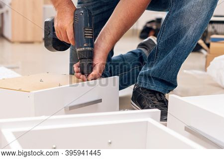Assembly Of Furniture, The Carpenter Screws A Self-tapping Screw Into A Drawer With A Screwdriver.