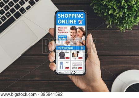 Online Shopping Sales. Woman Holding Cellphone With Mobile Shop App Buying Clothes Sitting At Wooden
