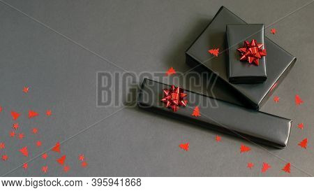 Handmade Christmas Gift Boxes Wrapped In Black Paper, Red Sparkle Ribbons And Festive Confetti. Care