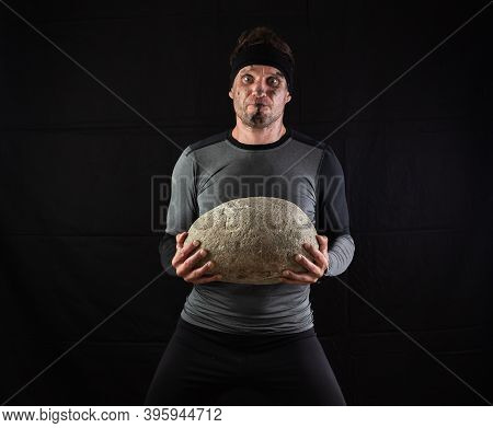 Sporty Man Holding A Large Heavy Stone In His Hands On A Black Background.