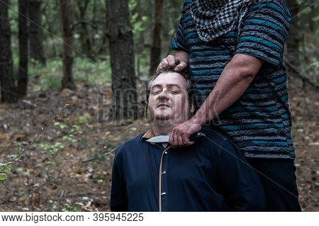 A Terrorist In A Blue T-shirt Puts A Knife To The Hostage's Throat. Victim Of Crime. The Concept Of