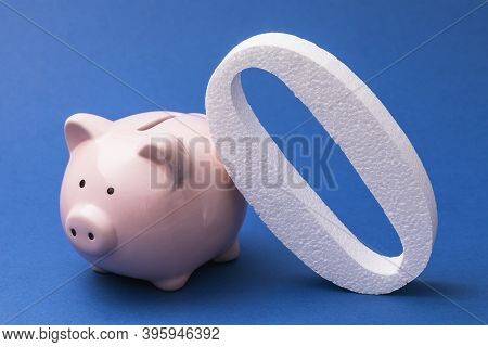 Zero And Piggy Bank On A Blue Background. Concept On The Topic Of Zeroing Deposits And Savings