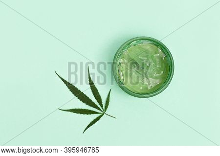 Jar With Transparent Cosmetic Product, Gel Or Cream With Cannabis Oil On Blue Colored Background. Fl