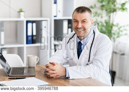Professional Help. Portrait Of Smiling Handsome Middle Aged Doctor Sitting At Desk With Laptop At Mo