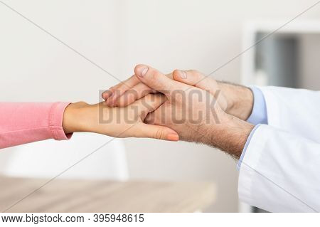 Empathy And Encouragement Concept. Close Up Of Male Doctor Comforting Female Patient, Holding Hands