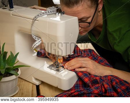 A Woman Of About Thirty In Glasses Sews On A Sewing Machine On A Wooden Background. Sewing And Handi