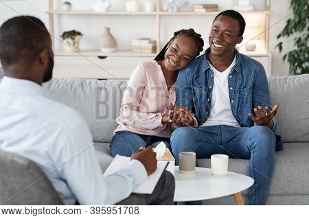 Family Counseling. Young Happy Black Couple Sitting On Couch At Psychotherapists Office, Holding Han