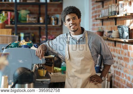 Friendly Meeting In Favorite Cafe In Morning. Smiling Young African American Barista Guy In Apron St