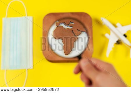 Plane Model, Face Mask, Loupe In Hand And Earth Model On A Yellow Background. Flight Impact Of Coron