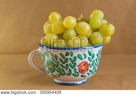 Bunch Of Grapes Presented In A Traditional Hand-painted Ceramic Pot