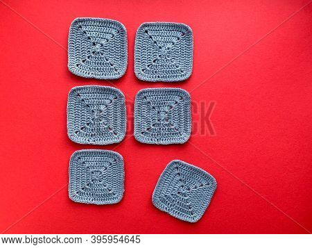 Crocheting. In The Photo, Knitted Elements Are Gray On A Red Background. Photo From Above. The Conce