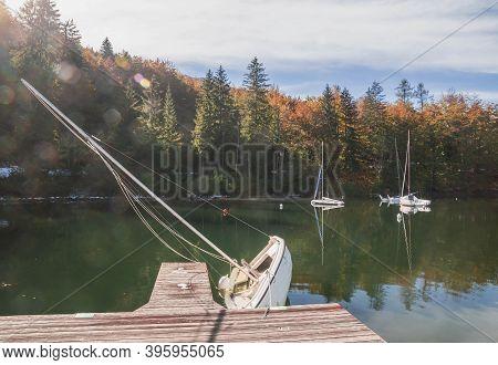 Capsized Sailboat Near The Pier On Lake Bohinj. Autumn Landscape In Slovenia