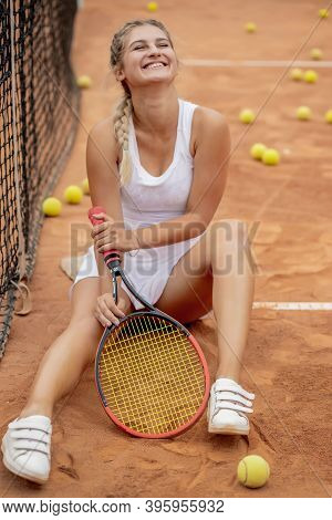 Happy Smiling Girl Is Chilling Near Tennis Net At Tennis Court With Racquet In Hands.