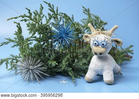 White Bull Toy. The Bull Is A Symbol Of The New Year 2021. Coniferous Branch With A Bull On A Blue B