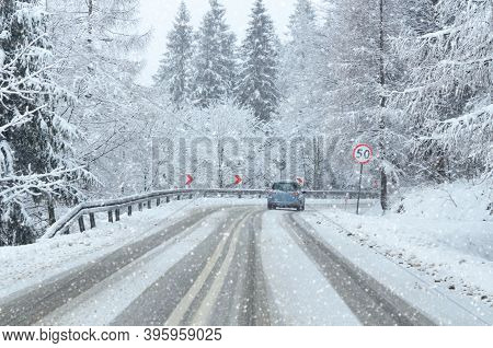 Driving A Car During A Bad Winter Weather On Snow-covered Mountain Road
