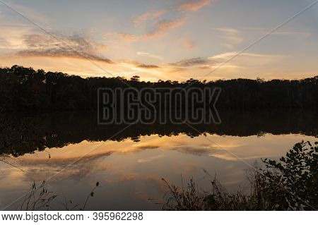 Reflection Like Glass Of A Sunset And Clouds On The Surface Of Yates Mill Pond In Raleigh, North Car