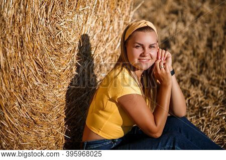 A Young Beautiful Girl In A Field Stands Near A Sheaf. Vacation In The Village. Young Woman In Yello