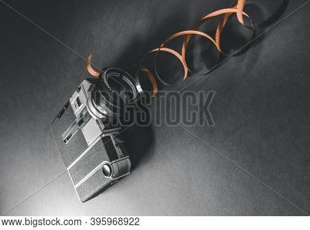 Vintage Analog Camera With Filmstrip On Gray Background