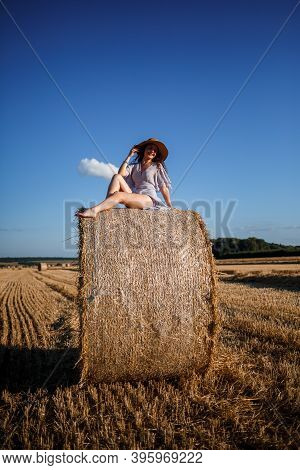 A Beautiful Young Woman In A Hat And A Summer Dress Sits On A Sheaf Of Hay In A Field. Rural Nature,