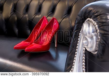 Pair Of Beautiful Red High-heeled Shoes. Red Shoes With Heels. Women's Shoes On A Leather Sofa.