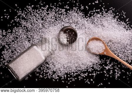 Sea Salt. Scattered Crystals Of White Sea Salt On A Black Background. Salt Shaker With Salt And Wood