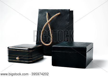 Black Gift Boxes With Golden Decoration And Gift Bag With Golden Strap Isolated