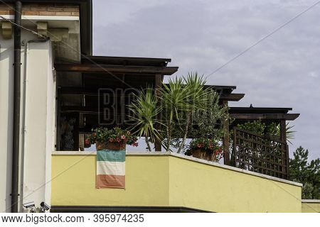 Home Balcony With Tricolor Flag. Patriotic Symbol In Italy At The Time Of Covid