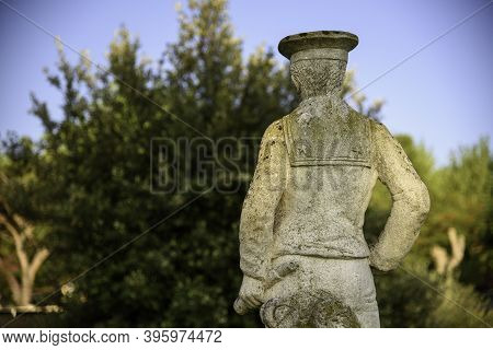 Half Bust Of An Old Statue In A Garden. Vintage Object With Sunset Light.