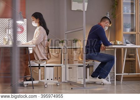 Side View Portrait Of Two People Wearing Masks In Office While Working At Desks In Separate Cubicles