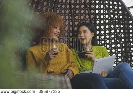 Two Woman Gossiping In The Swing. Lesbian Couple Relaxing And Drinking Red Wine. Close Up. High Qual