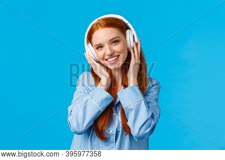 Technology, Lifestyle And People Concept. Cute Redhead Woman In Pyjama, Listen Music In Headphones,