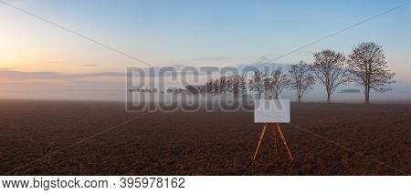 Blank Art Board And Realistic Wooden Easel On The Field. Landscape Covered With Fog In Central Bohem