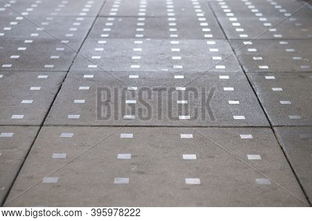 A Pathway In A City Paved With Concrete Blocks And Decorated With Metal Squares