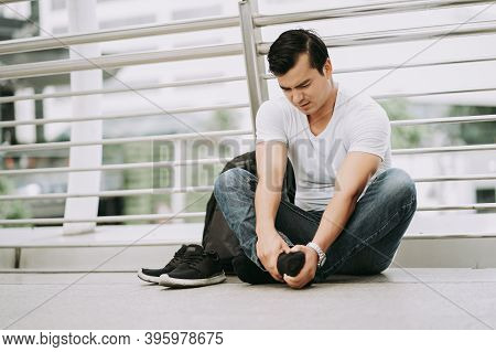 Traveling Asian Male Tourist Sitting On Street Ground While Suffering From Casual Shoes Due To Uncom